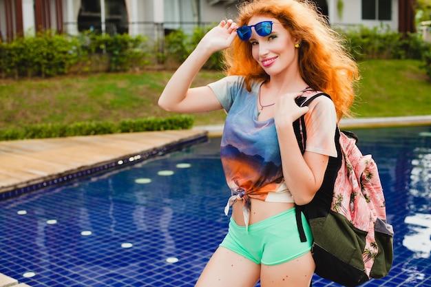 Jovem hippie ruiva magro indo para a academia, cabelo ruivo colorido, óculos de sol azuis, estilo esportivo, sardas, marcas de nascença, mochila, feliz, brincalhão, roupa legal, sorridente, sensual, atlético, roupa de fitness