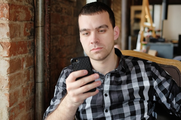Jovem hippie segurando um smartphone. trabalhador de escritório na hora do almoço falando ao telefone. um jovem bem-sucedido em uma camisa xadrez escura no café faz negócios. reunião de negócios.