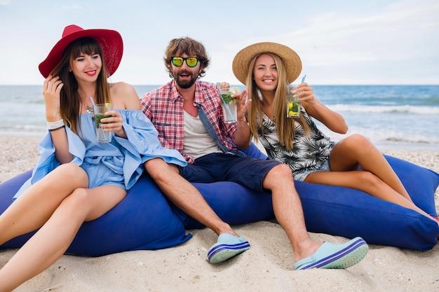 Jovem hippie sorridente com amigos felizes de férias sentados em pufes em uma festa na praia, bebendo um coquetel de mojito