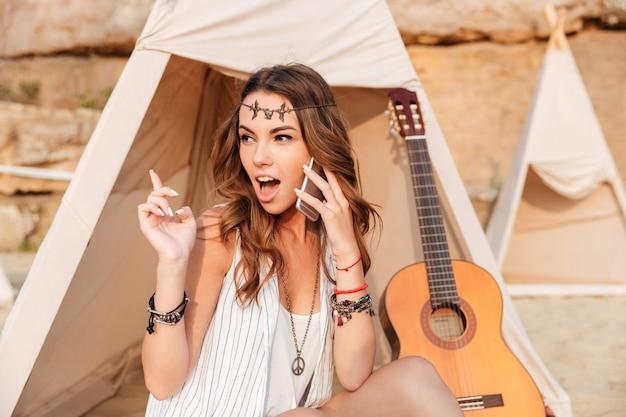 Jovem hippie sorridente em uma tenda na praia