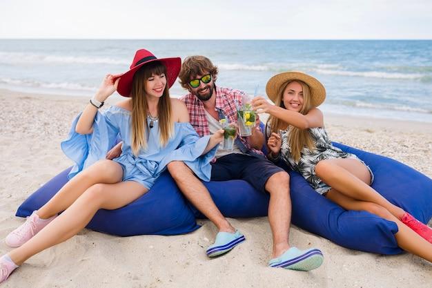 Jovem hippie sorrindo, amigos felizes nas férias de verão, sentados na praia com pufes, brindando, rindo, bebendo coquetel de mojito