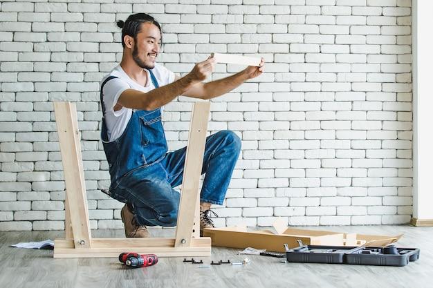 Jovem hippie trabalhando como faz-tudo, montando mesa de madeira com equipamentos, conceito para casa diy e self-service. no escritório há um bloco de tijolo branco.