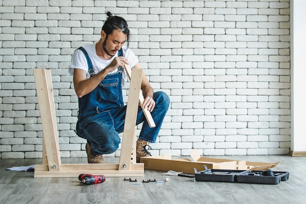 Jovem hippie trabalhando como faz-tudo, montando mesa de madeira com equipamentos e manual, conceito para casa diy e self-service com parede de bloco de tijolo branco ao fundo.