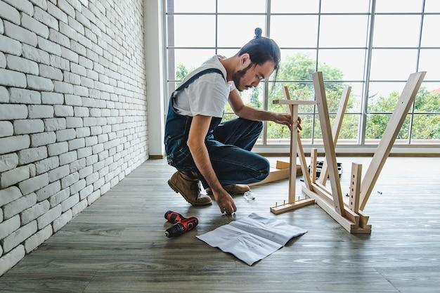 Jovem hippie trabalhando como faz-tudo procurando manual durante a montagem da mesa de madeira com equipamentos, conceito para casa diy e self-service. no escritório.