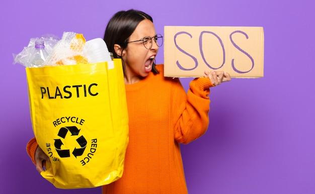 Jovem hispana com placa sos e plástico para reciclagem