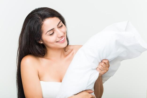 Jovem hispânica acordando e segurando um travesseiro