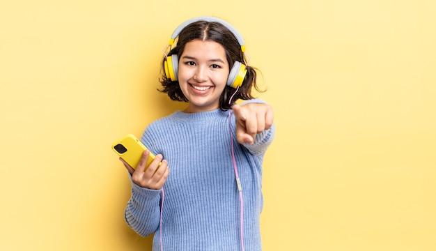 Jovem hispânica apontando para a câmera escolhendo você. conceito de fones de ouvido e smartphone