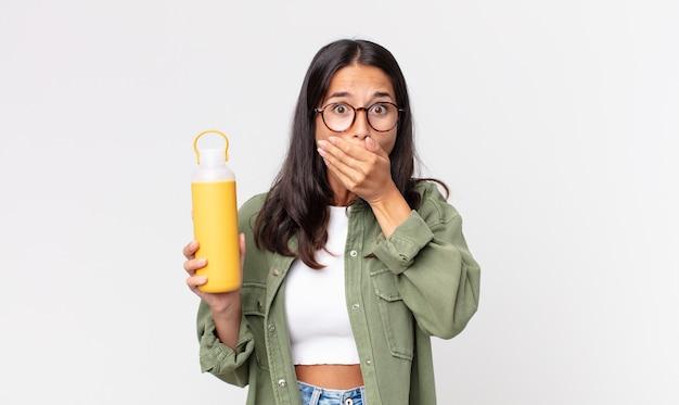 Jovem hispânica cobrindo a boca com as mãos com um choque e segurando uma garrafa térmica de café