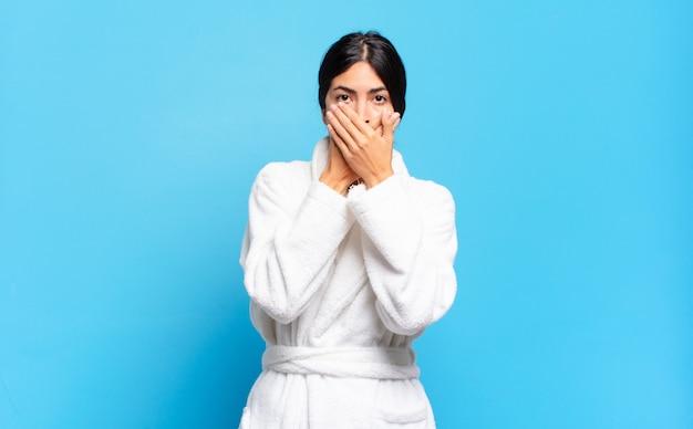 Jovem hispânica cobrindo a boca com as mãos com uma expressão chocada e surpresa, mantendo um segredo ou dizendo oops. conceito de roupão de banho