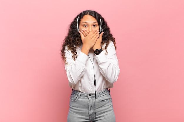 Jovem hispânica cobrindo a boca com as mãos com uma expressão chocada e surpresa, mantendo um segredo ou dizendo oops. conceito de telemarketing