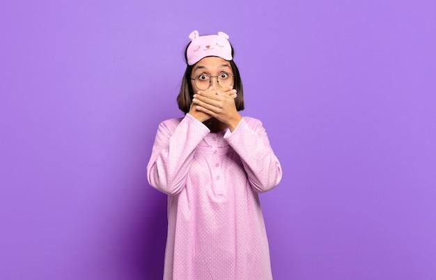 Jovem hispânica cobrindo a boca com as mãos com uma expressão chocada e surpresa, mantendo um segredo ou dizendo oops
