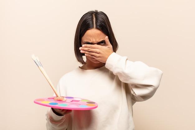 Jovem hispânica cobrindo o rosto com as duas mãos dizendo não! recusando fotos ou proibindo fotos