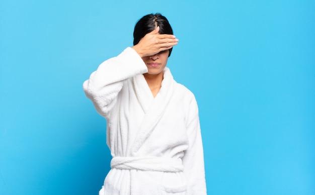 Jovem hispânica cobrindo os olhos com uma das mãos, sentindo-se assustada ou ansiosa, imaginando ou cegamente esperando por uma surpresa. conceito de roupão de banho
