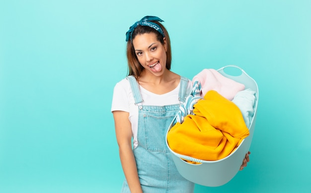 Jovem hispânica com atitude alegre e rebelde, brincando, mostrando a língua e lavando roupa