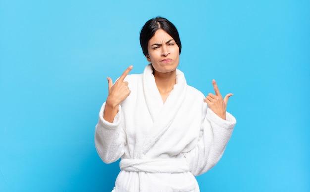 Jovem hispânica com uma atitude ruim, parecendo orgulhosa e agressiva, apontando para cima ou fazendo engraçado sinal com as mãos. conceito de roupão de banho