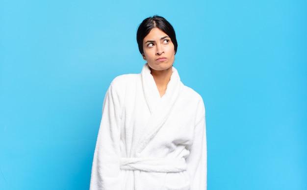 Jovem hispânica com uma expressão preocupada, confusa e sem noção, olhando para cima para copiar o espaço, em dúvida. conceito de roupão de banho