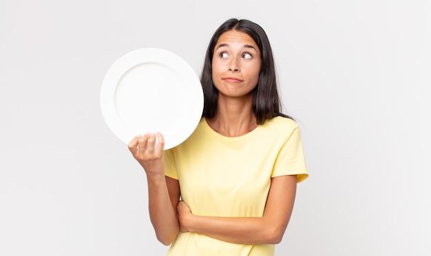 Jovem hispânica dando de ombros, sentindo-se confusa e insegura e segurando um prato vazio