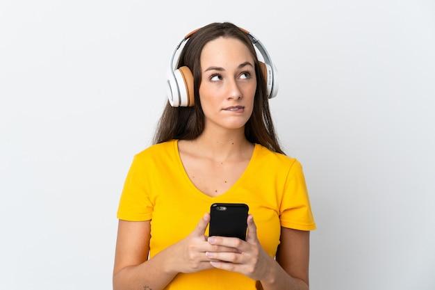 Jovem hispânica em um fundo branco isolado, ouvindo música com um celular e pensando
