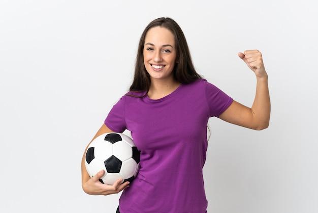 Jovem hispânica em uma parede branca isolada com uma bola de futebol comemorando uma vitória