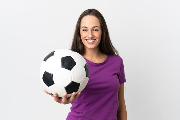 Jovem hispânica em uma parede branca isolada com uma bola de futebol