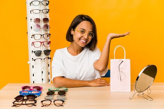 Jovem hispânica experimentando óculos isolados, mostrando um espaço de cópia na palma da mão e segurando a outra mão na cintura