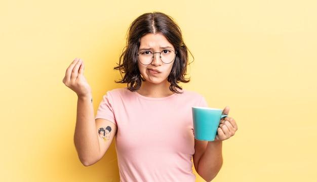 Jovem hispânica fazendo capice ou dinheiro gesto, dizendo para você pagar. conceito de caneca de café