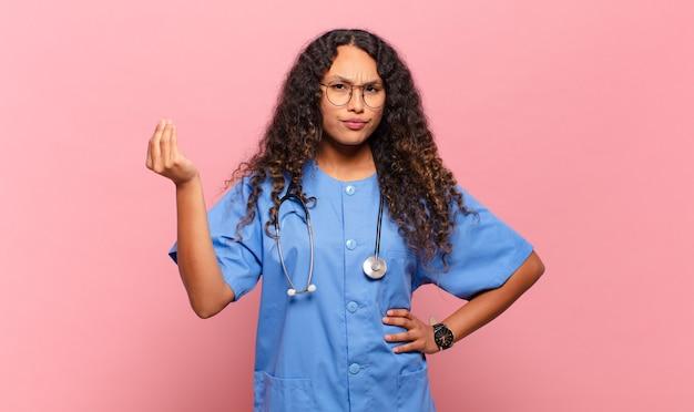 Jovem hispânica fazendo capice ou gesto de dinheiro, dizendo para você pagar suas dívidas !. conceito de enfermeira