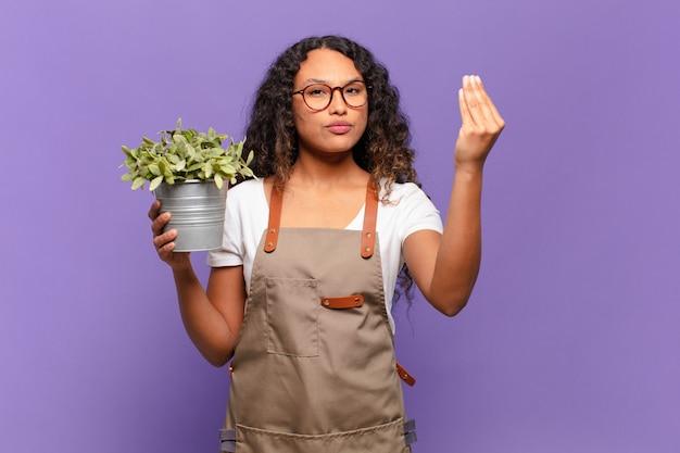 Jovem hispânica fazendo capice ou gesto de dinheiro, dizendo para você pagar suas dívidas !. conceito de jardineiro