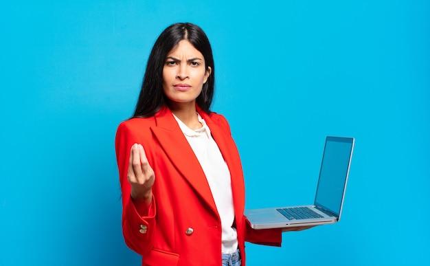 Jovem hispânica fazendo capice ou gesto de dinheiro, dizendo para você pagar suas dívidas !. conceito de laptop