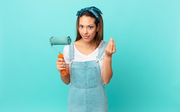Jovem hispânica fazendo um gesto de capice ou dinheiro, dizendo para você pagar e pintando uma parede