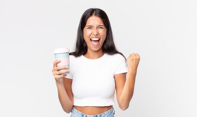 Jovem hispânica gritando agressivamente com uma expressão de raiva e segurando uma lata de café para viagem