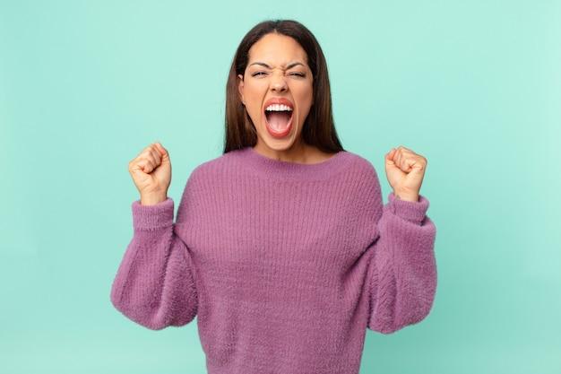 Jovem hispânica gritando agressivamente com uma expressão de raiva