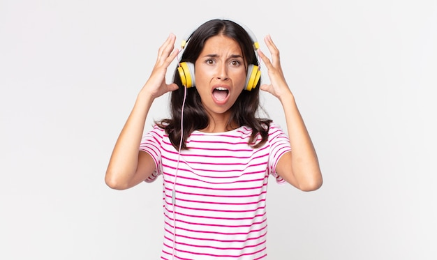 Jovem hispânica gritando com as mãos para cima ouvindo música com fones de ouvido