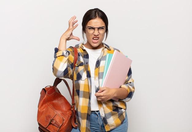 Jovem hispânica gritando com as mãos para o alto, sentindo-se furiosa, frustrada, estressada e chateada