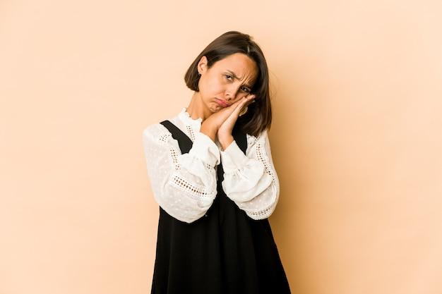 Jovem hispânica isolada bocejando mostrando um gesto cansado, cobrindo a boca com a mão.