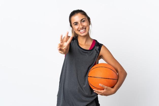 Jovem hispânica jogando basquete sobre um fundo branco isolado feliz e contando três com os dedos