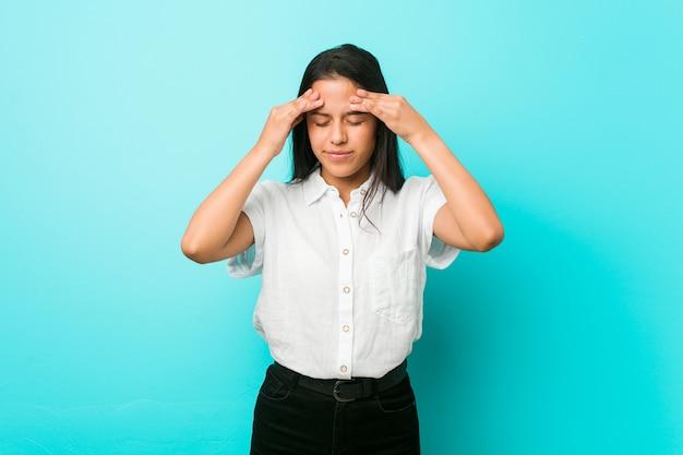Jovem hispânica legal contra uma parede azul, tocando as têmporas e tendo dor de cabeça.