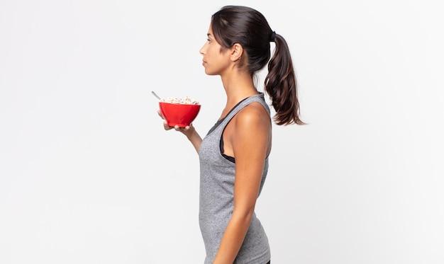 Jovem hispânica na vista de perfil, pensando, imaginando ou sonhando acordada. dieta de fitness e conceito de café da manhã