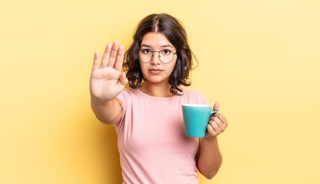 Jovem hispânica olhando sério mostrando a palma da mão aberta, fazendo o gesto de parada. conceito de caneca de café