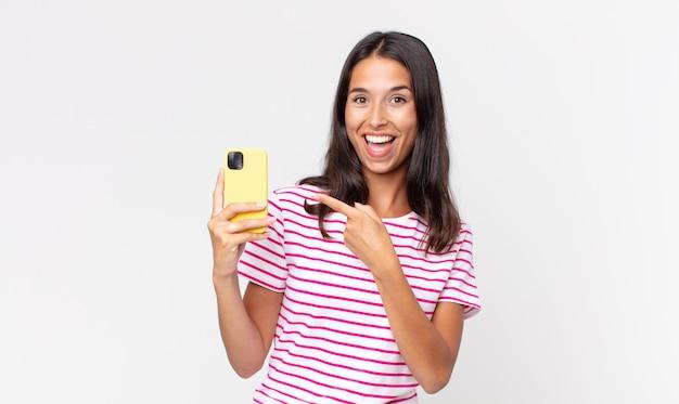 Jovem hispânica parecendo animada e surpresa, apontando para o lado e segurando um smartphone