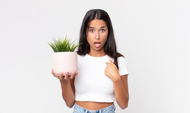 Jovem hispânica parecendo chocada e surpresa com a boca bem aberta, apontando para si mesma e segurando uma planta de casa decorativa