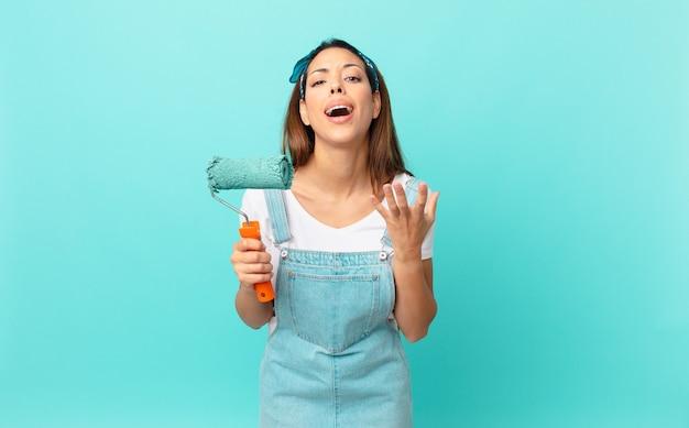 Jovem hispânica parecendo desesperada, frustrada e estressada pintando uma parede