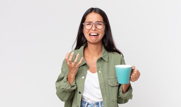 Jovem hispânica parecendo desesperada, frustrada e estressada, segurando uma caneca de café