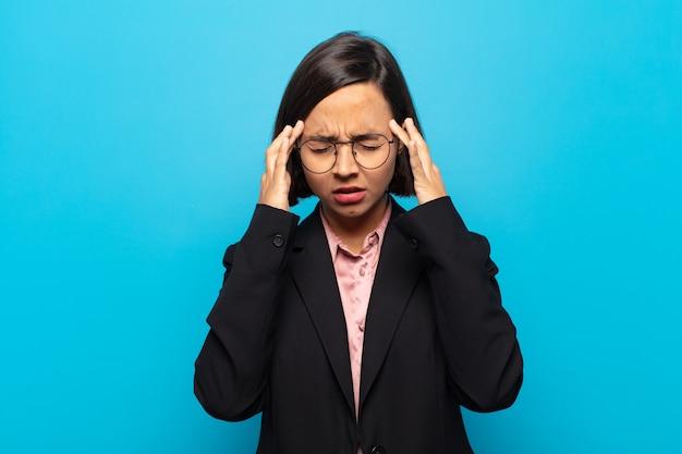 Jovem hispânica parecendo estressada e frustrada, trabalhando sob pressão, com dor de cabeça e preocupada com problemas