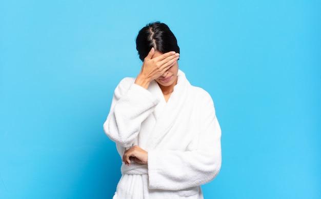 Jovem hispânica parecendo estressada, envergonhada ou chateada, com dor de cabeça, cobrindo o rosto com a mão. conceito de roupão de banho