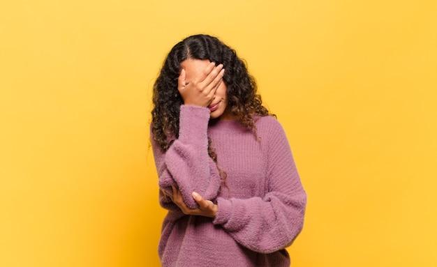 Jovem hispânica parecendo estressada, envergonhada ou chateada, com dor de cabeça, cobrindo o rosto com a mão