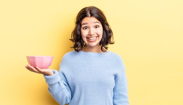 Jovem hispânica parecendo feliz e agradavelmente surpresa. conceito de tigela vazia