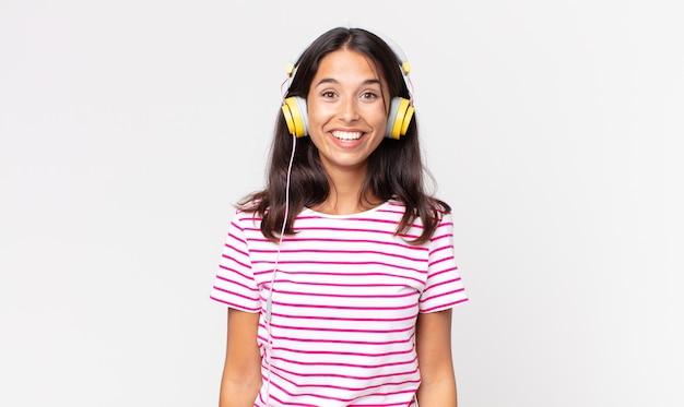Jovem hispânica parecendo feliz e agradavelmente surpresa ouvindo música com fones de ouvido