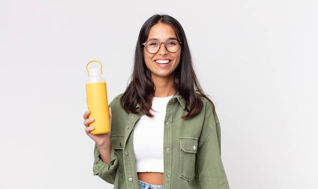 Jovem hispânica parecendo feliz e agradavelmente surpresa, segurando uma garrafa térmica de café