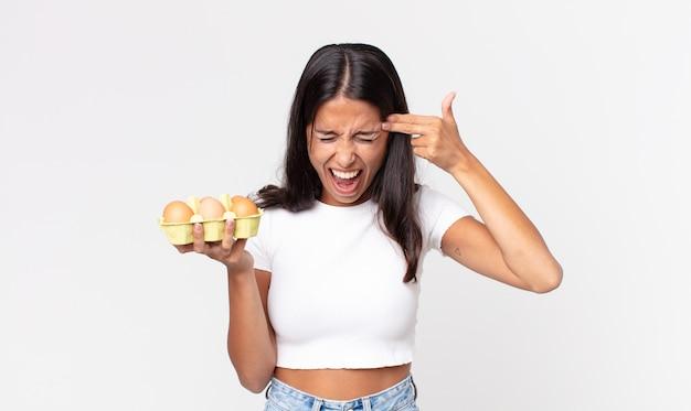Jovem hispânica parecendo infeliz e estressada, gesto suicida fazendo sinal de arma e segurando uma caixa de ovos